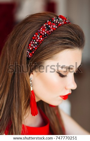 c6626b00569d5 Above view of beautiful brunette girl wearing in shiny red hand band and  long earrings.