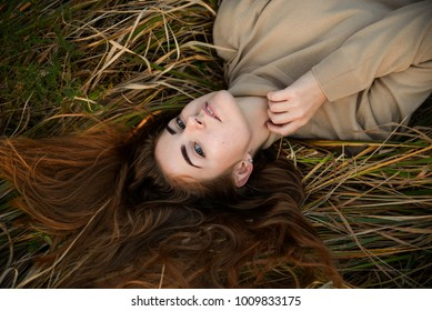 Above view of beautiful redhaired girl lying on grass, posing, embracing. Autumn forest with yellow grass. Woman with long hair, in jeans and blouse.