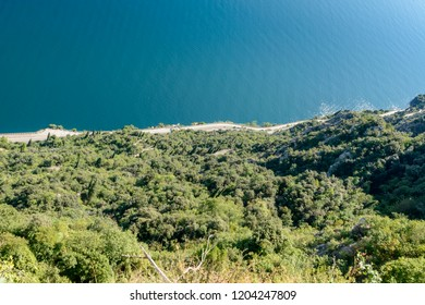 above view of bending lakeside panoramic road called western Gardesana, shot in bright fall light from Pieve, Brescia, Italy
