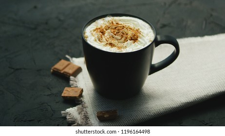 From above view of black mug of coffee with whipped cream on top and pieces of chocolate laid near on gray background