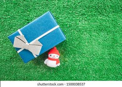 Above view of blue paper gift box with ribbon and snowman on lawn background with copy space. Christmas and New Year holiday present or Happy birthday. Greeting card style for Merry Xmas. Top view