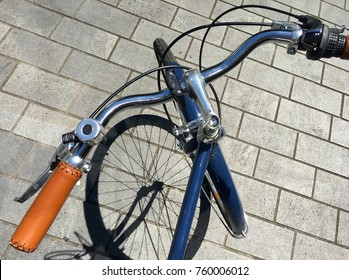 Above view of blue retro bicycle handlebar on a sunny day with shadow of the front wheel falling over a street floor tiles. Vintage transportation background travel concept Copy space