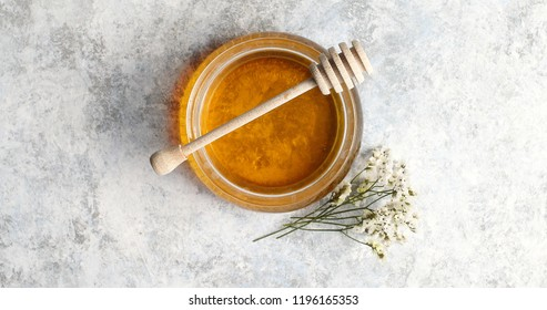 From above view of bowl full of yellow honey with spindle decorated with herb on white background
