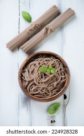 Above view of buckwheat soba noodles, white wooden surface