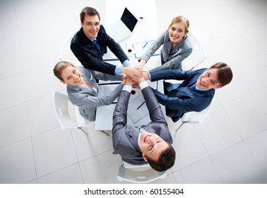 Above view of business people with their hands on top of each other looking at camera