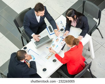 Above view of business team are sitting around table and working.