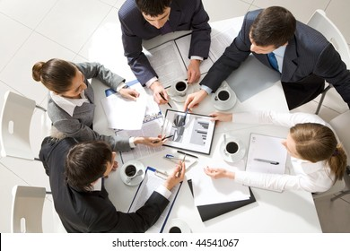 Above view of business team sitting around table and discussing working plan