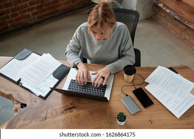 Above view of busy mature woman sitting at table with papers and devices and working hard in office