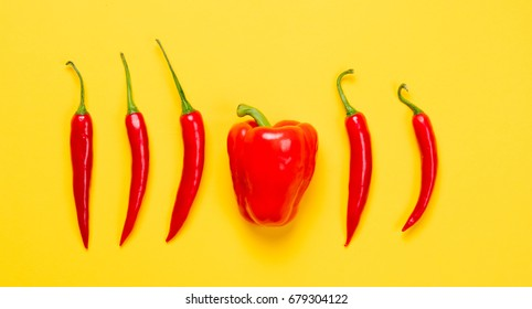 Above view at Chili pepper and Capsicum on yellow background