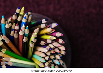above view of colored pencils in a jar against a maroon background