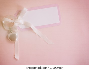 Above View of a Cute, Pink and White Notecard for a Baby Girl on a Cloth Background with room or space for copy, text, your words.  A Silver Heart Shape Teething Ring.  Horizontal Instagram light.
