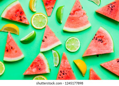 Above view at cutted lemons and limes with watermelon on green background