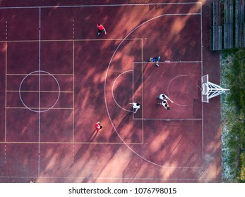 Above view of determined basketball players in action, playing on a red paved court
