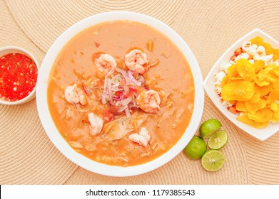 Above view of Ecuadorian food: shrimp cebiche with some chifles inside white bowl, lemon and red spicy salad inside a white bowl in a wooden table background