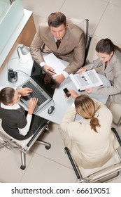 Above view of executive business group sitting at desk in office and working