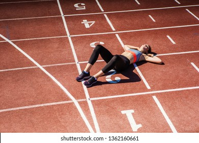 From above view of exhausted teen athlete in sportswear resting on track after finishing tough race