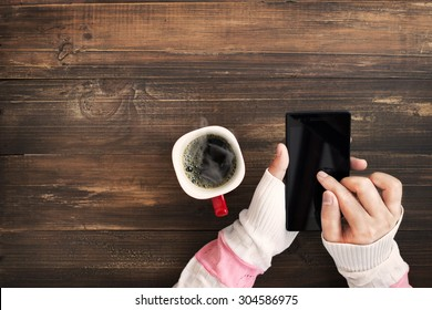 Above view of female hand holding smart phone with hot cup of coffee on wood table. Photo in vintage color image style.