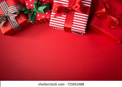 From above view of few wrapped beautiful gifts decorated with colorful ribbons and composed on red.