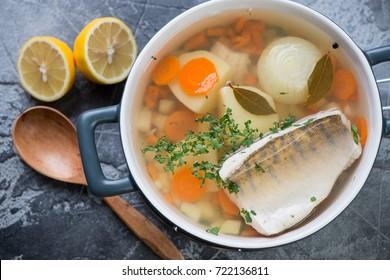 Above view of fresh fish soup or russian ukha with sudak, closeup, studio shot