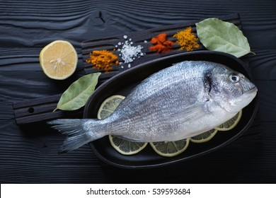 Above view of fresh uncooked dorado fish with various condiments over black wooden surface