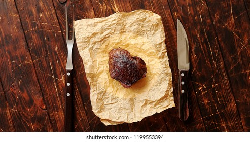 From above view of fried piece of meat laid on paper napkin with knife and fork placed near on wooden background