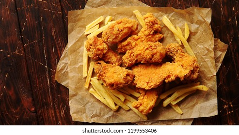 From above view of fried pieces of meat and potatoes laid on paper napkin on wooden background