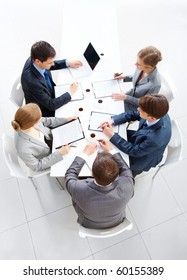 Above view of friendly workteam discussing papers at meeting