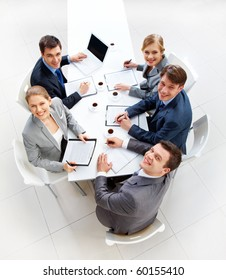 Above view of friendly workteam looking at camera during meeting