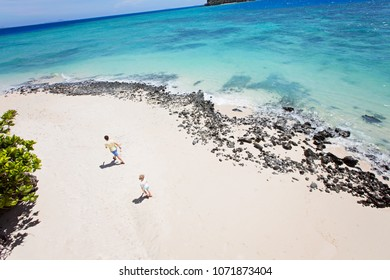 above view of gorgeous rocky white sand beach with turquoise lagoon and family of two, father and son, walking and enjoying family vacation together