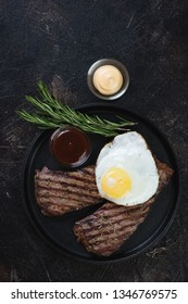 Above view of grilled beef schnitzels with fried egg and dipping sauces over dark brown stone surface