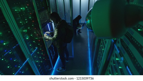 From above view of hackers entering server room and breaking into hardware system with security camera capturing them