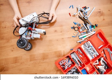 From above view of hands of incognito kid holding robot and working on project, details in box. Colorful pieces from building kit for children on table. Concept of science engineering.