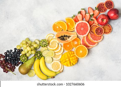 Above view of healthy fruits in rainbow colours, strawberries, mango, grapes, bananas, grapefruit on the off white table, copy space for text, selective focus