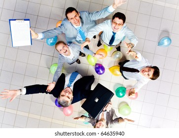 Above view of joyful business people looking at camera with balloons on the floor