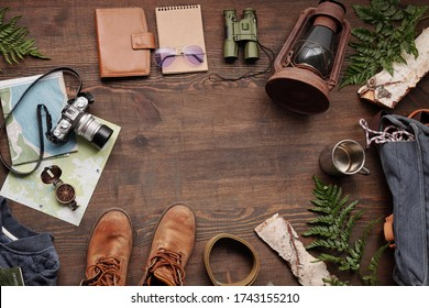 Above view of lantern, binoculars, sketchpad, purse, camera, maps, boots, belt and green twigs in circle on wooden table
