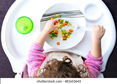 Above view of a little toddler child eats vegetables. Childhood and children health care concept. Real people. copy space