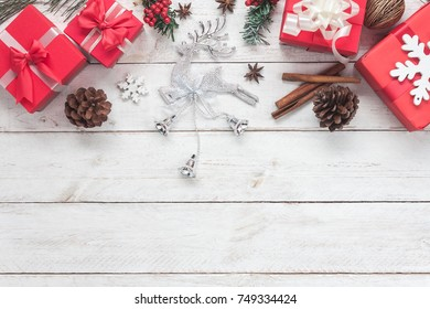 Above view of Merry Christmas decorations & Happy new year ornaments concept.Essential difference objects on modern rustic wood white background at home studio office desk.Glass reindeer with items.