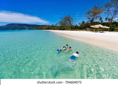Above view of  mother and kids snorkeling in a clear tropical water near exotic white sand beach