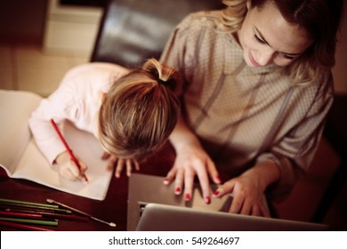 Above view of mother using laptop and her little daughter drawing at home.