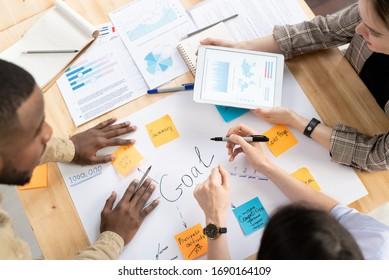 Vue d'dessus de collègues multiethniques autour du bureau et travaillant ensemble sur un plan d'affaires lors d'une réunion