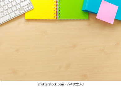 Above view of office workplace with blank desk space. Colorful paper book, keyboard, folder and pink sticky note on top side. Documents and time management concepts, mockup background flame.