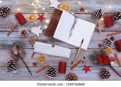 Above view on chaotic arranged christmas and winter decorated table with note pad and light chain shining, including copy space