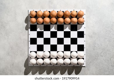 From above view on a chessboard with figures of white and brown eggs on a gray background. Creative Idea Easter and chess