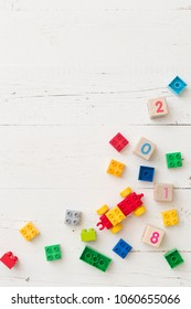 Above view on colorful plastic toy blocks, wooden cubes with numbers on white wooden background.