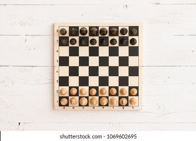 Above view on wooden chessboard with figures ready for the game.