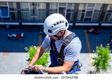 Above view on young man, industrial climber at work, he washing building facade.
