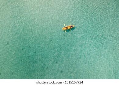 Above view of pair kayaking in azure waters of Caribbean sea