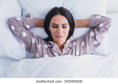 Above view portrait of adorable satisfied girl lying on back arms behind head closed eyes free time indoors
