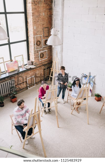 Above view portrait of adult students  painting sitting by easels in art studio with female art teacher watching them in spacious sunlit loft space, copy space