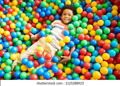 Above view portrait of cute African-American boy in ball pit smiling happily at camera while having fun in children play center, copy space